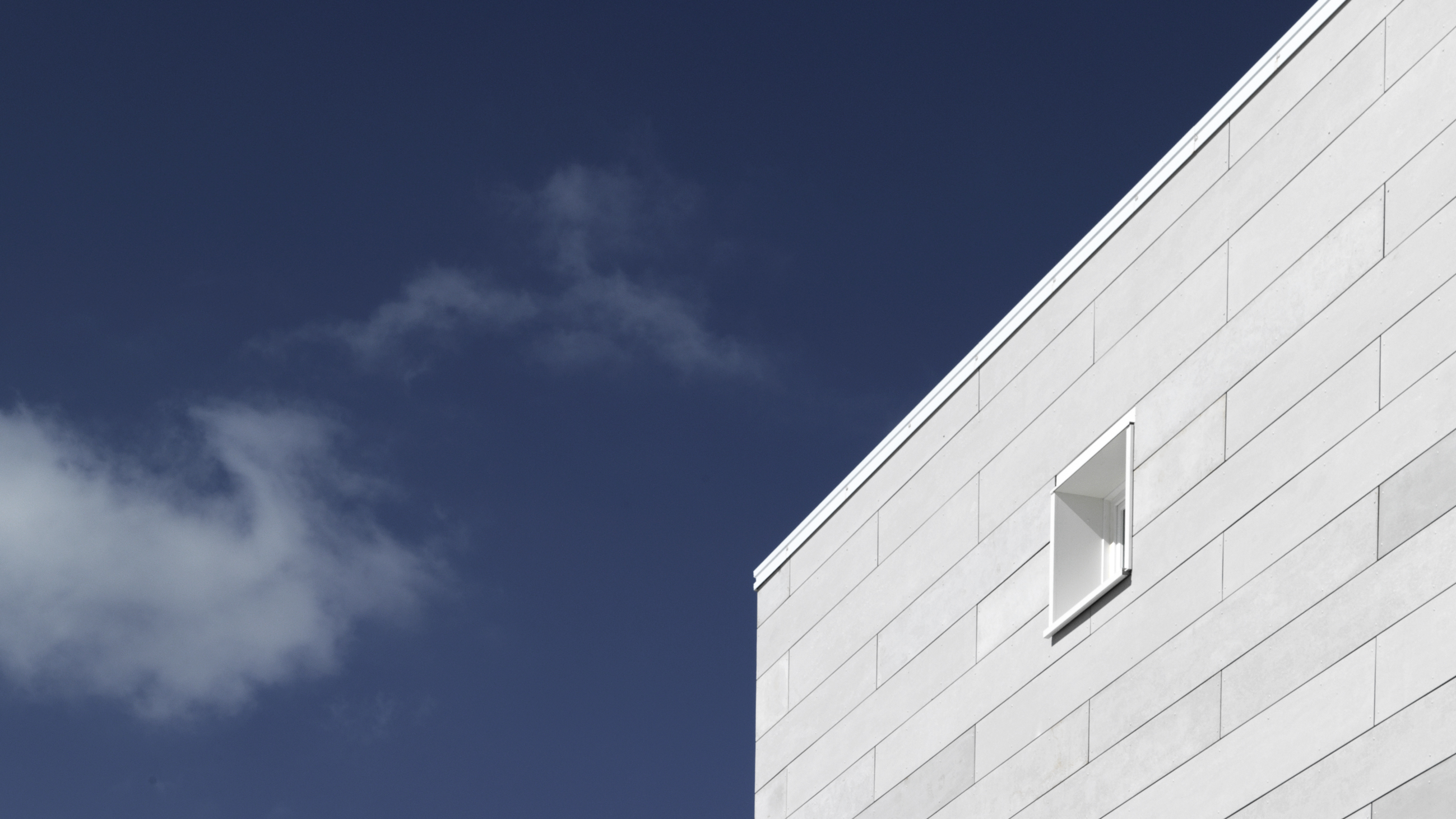 a wall with one window, in background the sky